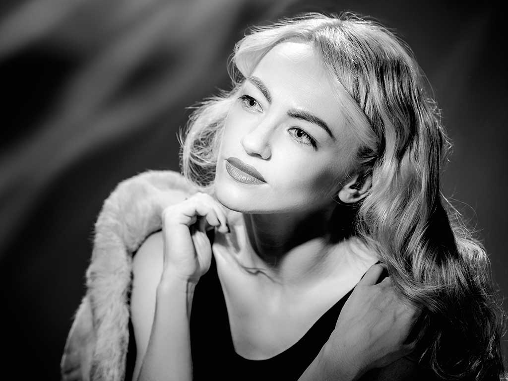 Black and white portrait of beautiful woman in vintage style with fur coat